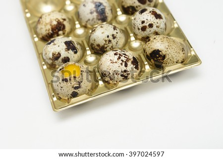 Quail eggs in a golden plastic container / tray isolated on a white background,Kerala, India. egg cut open , yellow yolk  - stock photo