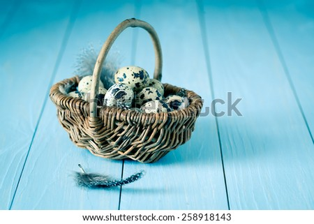quail eggs in a wicker basket on blue wooden background - stock photo