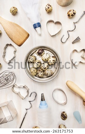 quail eggs in metallic bowl and easter baking tools on white wooden background, top view - stock photo