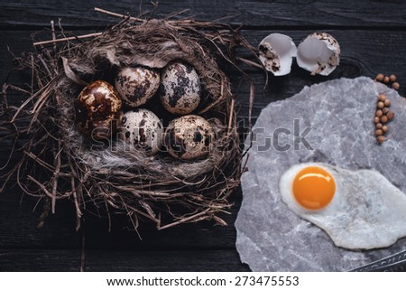 Quail eggs in the nest and a fried egg on a wooden board. Low contrast. Instagram toned. - stock photo