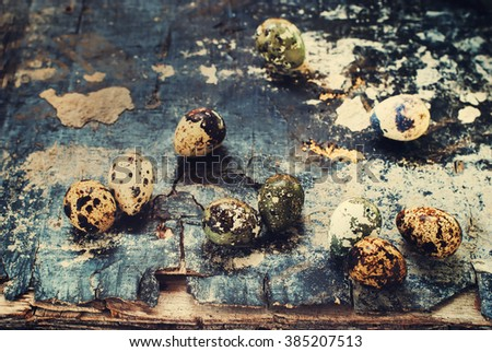 Quail Eggs Scattered on Old Shabby Vintage Table Damaged Background Selective Focus Toned Easter Kinfolk Style Natural Rural Style - stock photo