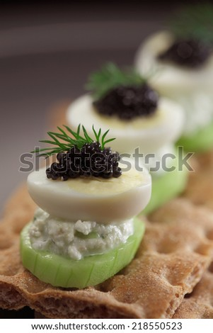 Quail eggs with black caviar crispbread - stock photo