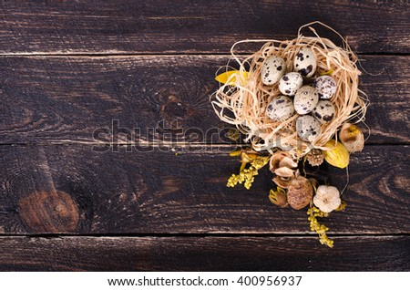 Quail nest with spotted eggs, dried plants on a wooden  background. Free space for your text. - stock photo