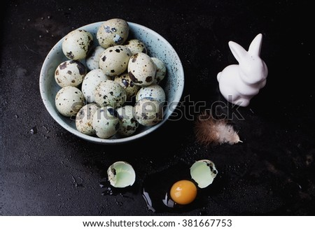 Quails Eggs  and white ceramic bunny with yellow tulip flowers on an old spotted bowl against a rustic background with selective focus. A different type of concept image for Easter. - stock photo