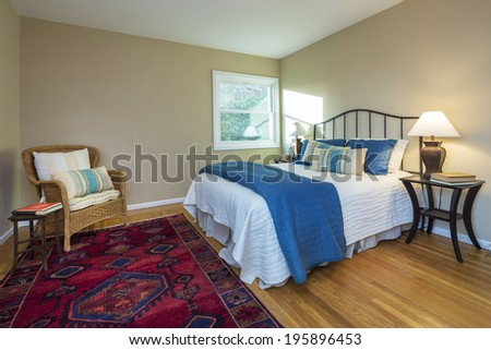 Quaint Bedroom in beige with chair, bedside lamps, red ornamented rug and vintage furniture. - stock photo
