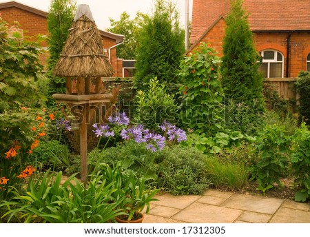 Quaint English Cottage Garden With Chapel In the Background - stock photo