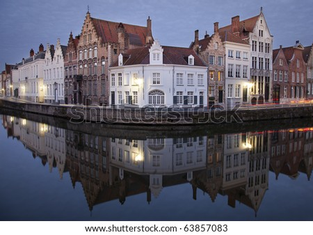 Quaint European buildings along a quiet canal at daybreak. Bruges, Belgium. - stock photo