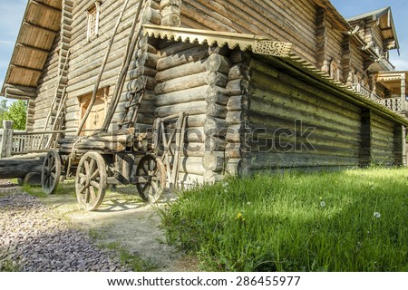 quaint, traditional Russian log house, in the yard on the green grass is a cart with logs on a sunny summer day - stock photo