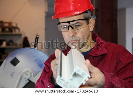 Quality Control of Plastic Parts for Window.Engineer controlling plastic extrusion profile for window. - stock photo