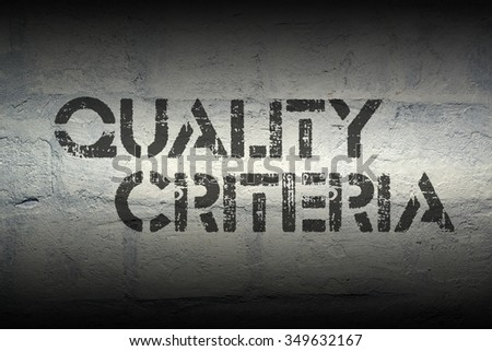 quality criteria stencil print on the grunge white brick wall - stock photo