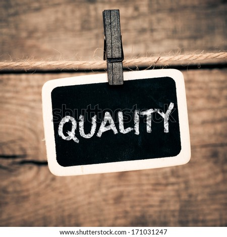 Quality handwritten with white chalk onold photo and clothes peg on a wooden background - stock photo