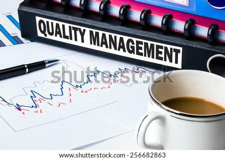 quality management label on business document folder - stock photo