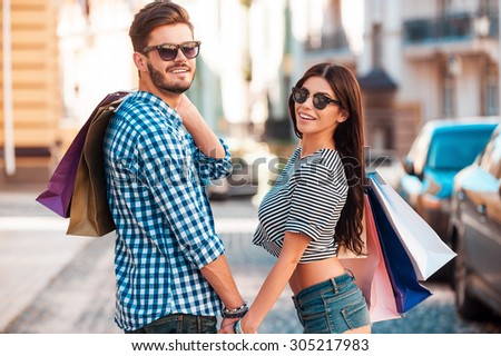Quality time together. Beautiful young loving couple carrying shopping bags on shoulders and holding hands while walking along the street  - stock photo