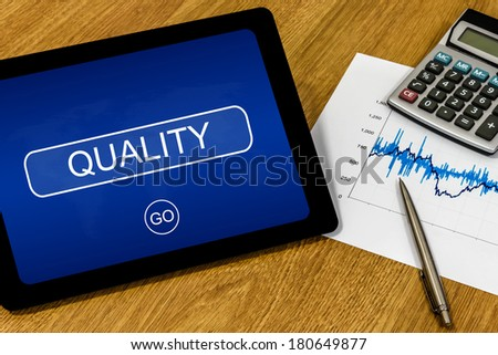 Quality word on digital tablet with calculator and financial graph - stock photo