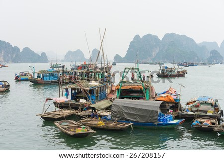 Quang Ninh, Vietnam - Mar 22, 2015: Fishing village in Bai Tu Long bay, next to Ha Long bay. Many people with their family doing trading and fishing on boat - stock photo