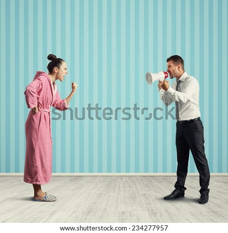 quarrel between dissatisfied wife and angry husband with megaphone - stock photo
