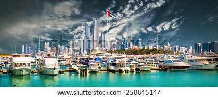 quay with yachts and skyscrapers in Abu Dhab against blue sky - stock photo