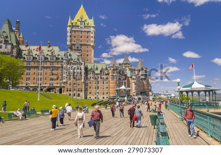 QUEBEC CITY, QUEBEC, CANADA -  MAY 30, 2004: Le Chateau Frontenac castle and hotel, with people walking along Dufferin Terrace boardwalk, a National Historic Site, in Old Quebec City. - stock photo