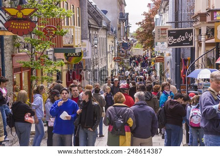 QUEBEC CITY, QUEBEC, CANADA - MAY 29, 2004:  Tourism on Petit Champlain Street, in Old Quebec City. People walk along the narrow street shopping for souvenirs. - stock photo