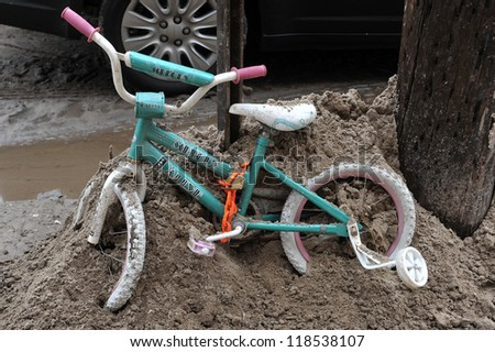 QUEENS, NY - NOVEMBER 11: Kids bycicle stays chaned to the street pole in the Rockaway area after Hurricane Sandy in Queens, New York, U.S., on November 11, 2012. - stock photo