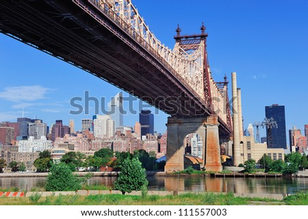 Queensboro Bridge in Midtown Manhattan with New York City skyline over East River as the famous landmarks viewed from Brooklyn. - stock photo