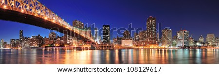 Queensboro Bridge over New York City East River at sunset with river reflections and midtown Manhattan skyline illuminated. - stock photo