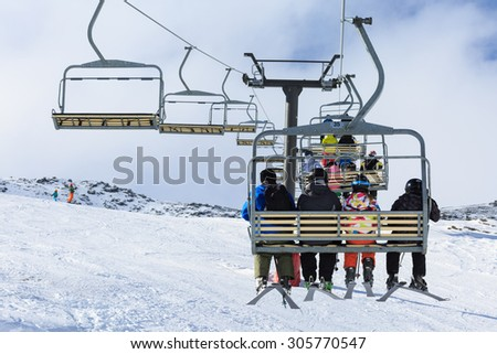 QUEENSTOWN, NEW ZEALAND - AUGUST 6: Unidentified skiers  ride the ski chair lift up the Remarkables Ski Area on August 6 2015 in Queenstown, South Island, New Zealand - stock photo