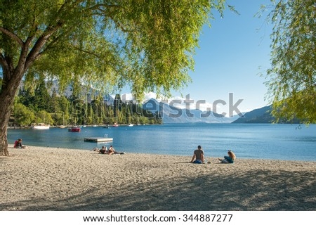 QUEENSTOWN, NEW ZEALAND - FEBRUARY 15: Tourists relax at the shore of Lake Wakatipu on February 15, 2012 in Queenstown. Queenstown is famous as a center of adventure tourism.  - stock photo