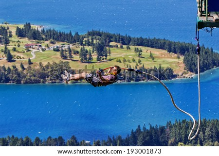 QUEENSTOWN,NEW ZEALAND - JANUARY 11, 2013: a tourist braves the Ledge Bungy. Situated 400m above the town, the popular attraction offers night jumps. - stock photo