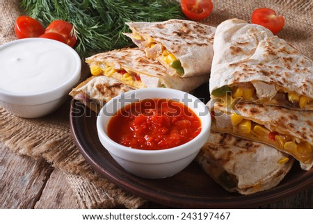 Quesadilla sliced with vegetables, chicken on a plate closeup and sauces. horizontal  - stock photo