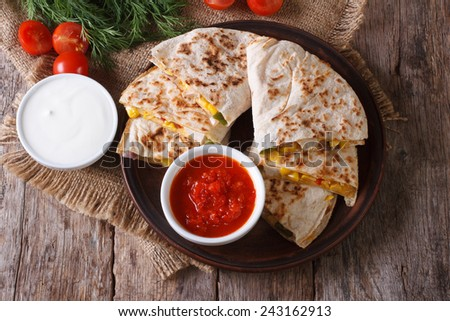 Quesadilla with vegetables and sauces close-up on the table. horizontal view from above  - stock photo