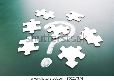 Question mark and puzzle pieces on blackboard - stock photo
