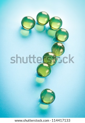 Question mark from oil capsule on blue background - stock photo