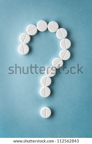 Question mark  from pills  on blue background - stock photo