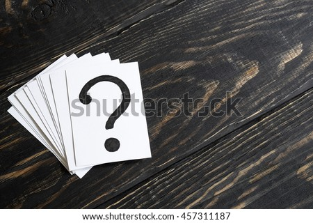 Question mark heap on table concept for confusion, question or solution on wooden background on the left - stock photo