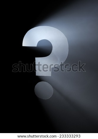 Question Mark. Hole cut in cardboard, smoke machine and spotlight. The image may appear noisy, but that is the texture of the smoke. - stock photo