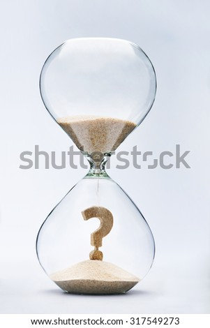 Question Mark made out of falling sand inside hourglass - stock photo