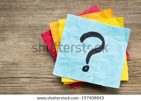 question mark on a sticky note against grained wood - stock photo