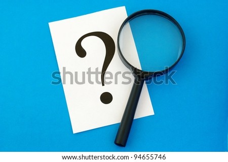 question mark on the paper and a magnifying glass - stock photo
