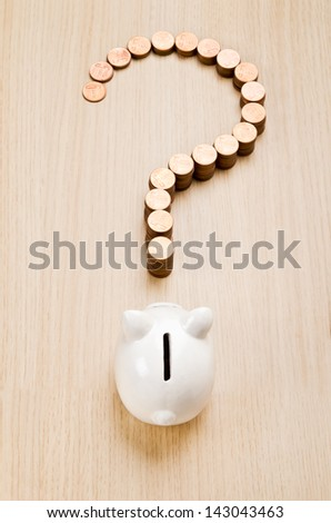 Question mark sign made out of coins in front of a piggy bank - stock photo