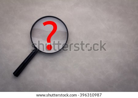 question mark under a magnifying glass with grey background - stock photo