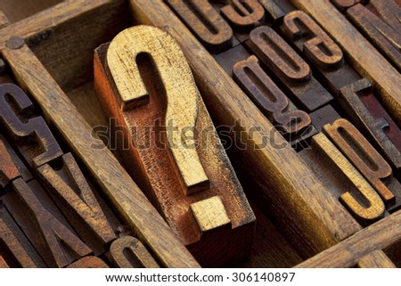 question mark - vintage wooden letterpress type block in old typesetter drawer among other letters stained by color inks - stock photo