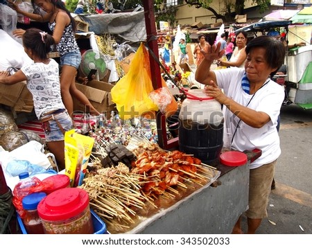 QUEZON CITY, PHILIPPINES - NOVEMBER 22, 2015: A woman sells cold juice and a variety of barbecue on a cart at a street in Quezon City, Philippines - stock photo