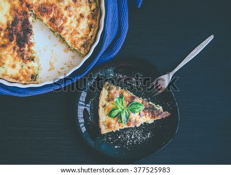 Quiche lorraine pie with chicken, mushrooms and broccoli in blue round baking form on wooden background. A piece of French quiche Lorraine on the plate with the fork. Top view. Mystic light style. - stock photo