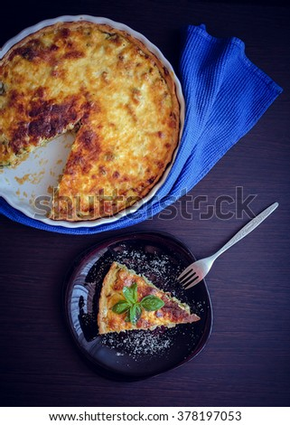 Quiche lorraine pie with chicken, mushrooms and broccoli in blue round baking form on wooden background. A piece of French quiche Lorraine on the plate with the fork. Vertical. Top view. - stock photo