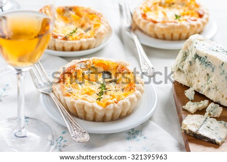 quiche with pumpkin and blue cheese. French cuisine. table set, plates, glasses with wine - stock photo