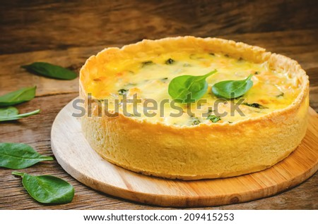 quiche with salmon and spinach on a dark wood background. toning. selective focus on the front of the pie - stock photo