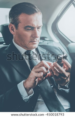 Quick business message. Confident mature businessman typing message on his smart phone while sitting on the back seat of a car - stock photo