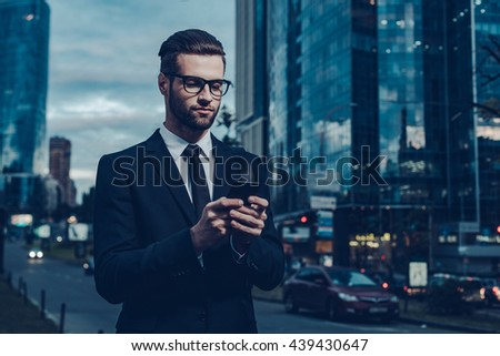 Quick business message. Night time image of confident young businessman in formalwear holding smart phone and looking at it while standing outdoors with cityscape in the background - stock photo