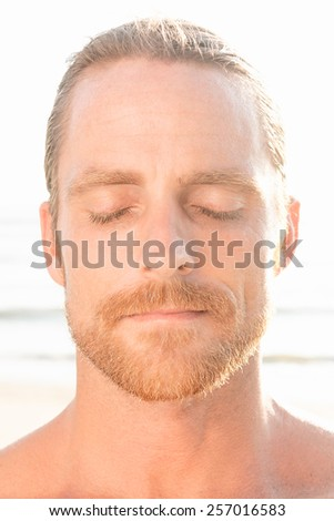 Quiet meditative handsome man with a beard standing at the beach in the tropical sunshine with his eyes closed in peace and tranquility - stock photo